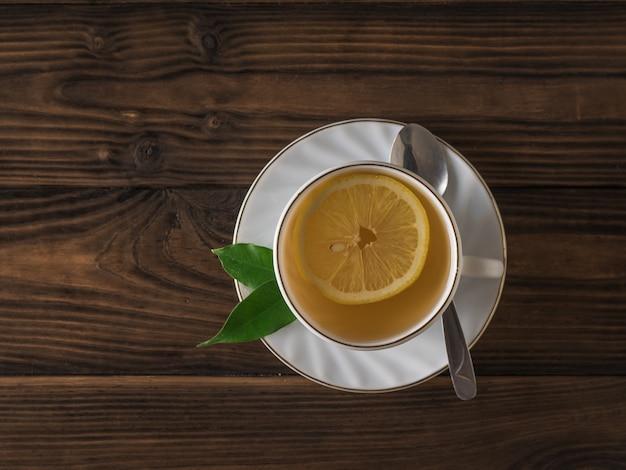 Una fetta di limone in una tazza di tè bianca e un cucchiaio di metallo su un tavolo di legno. una bevanda tonificante utile per la salute.