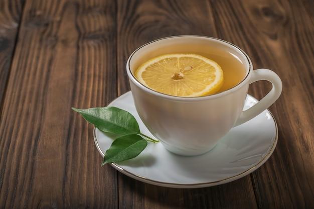 Una fetta di limone in una tazza di tè bianca su un tavolo di legno. una bevanda tonificante utile per la salute.