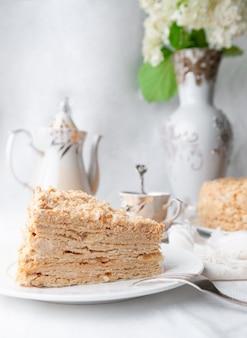 Fetta di torta napoleone multistrato con crema al burro su un piatto bianco primo piano accanto a un piatto c'è un tovagliolo e una forchetta sullo sfondo c'è una tazza teiera e un vaso di fiori sfondo sfocato