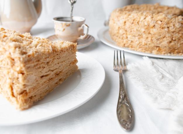 Fetta di torta napoleone multistrato con crema al burro su un piatto bianco primo piano accanto a un piatto c'è un tovagliolo e una forchetta sullo sfondo c'è una tazza teiera e un vaso di fiori sfondo bianco