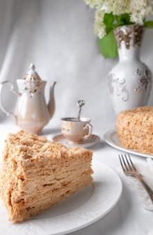 Fetta di torta napoleone multistrato con crema al burro su un piatto bianco primo piano c'è un tovagliolo e una forchetta vicino a un piatto sullo sfondo c'è una tazza di teiera e un vaso di fiori sfondo grigio