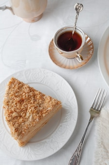Fetta di torta napoleone multistrato con crema al burro. su un piatto bianco. vista dall'alto. vicino a un piatto ci sono un tovagliolo, una forchetta, una tazza di tè, un vaso di tè con fiori. sfondo bianco.