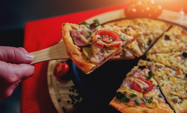 Una fetta di pizza in mano. un ristorante.