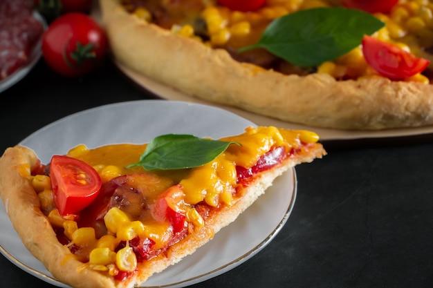 Fetta di pizza con ciliegia e basilico su sfondo nero ingredienti per la preparazione del cibo nazionale italiano
