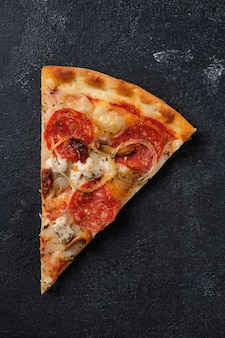 Una fetta di pizza con pomodori secchi salsiccia piccante pollo cipolle funghi miele mozzarella