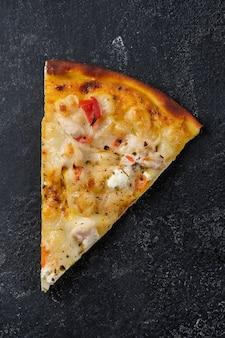 Un trancio di pizza con pomodori pollo cipolle feta mozzarella e spezie