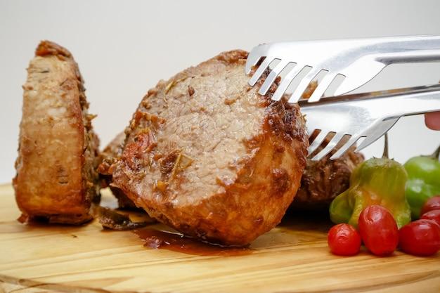 Fetta di carne cotta in pentola su tavola di legno con coltello e posate