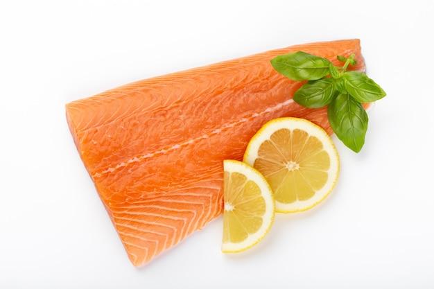 Fetta di salmone pesce rosso con limone, basilico isolato su bianco