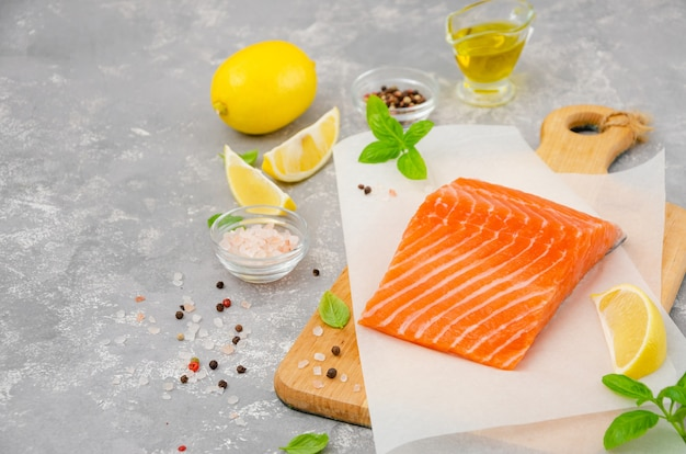 Fetta di salmone pesce rosso con limone, olio d'oliva, basilico fresco e spezie su una tavola di legno su un muro grigio. copia spazio.