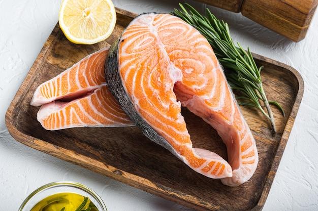 Fetta di trota di pesce rosso con erbe aromatiche, su sfondo bianco.
