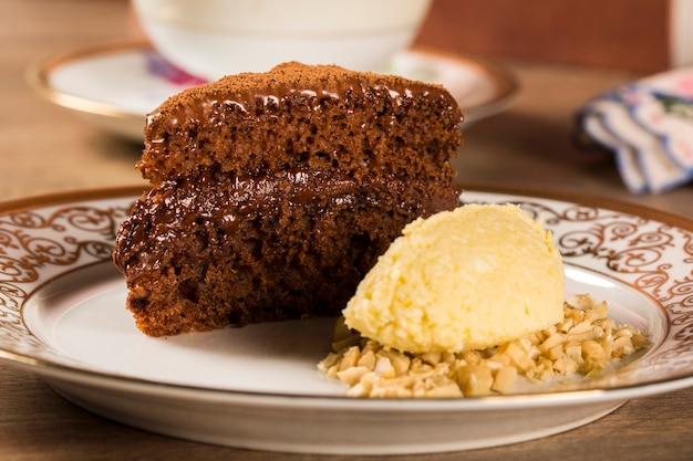 Una fetta di torta al cioccolato ricca con gelato e caffè sul tavolo