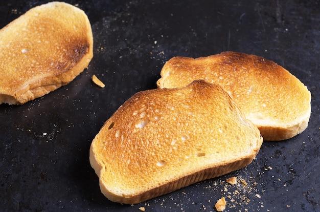 Fetta di pane bianco arrostito su sfondo nero da vicino