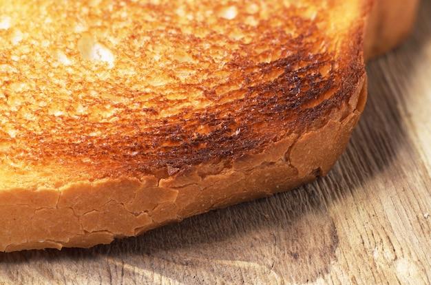 Fetta di pane bianco arrostito su fondo di legno. foto macro