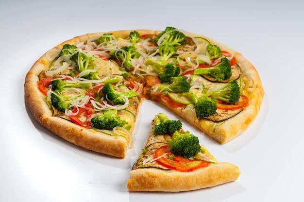 Fetta di una pizza vegetariana separata su sfondo bianco, con salsa di pomodoro, broccoli, pomodori, zucchine, melanzane e anelli di cipolla