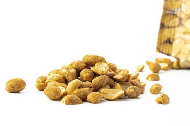 Fetta di noci piccanti con pepe in primo piano, snack per birra isolato su sfondo bianco