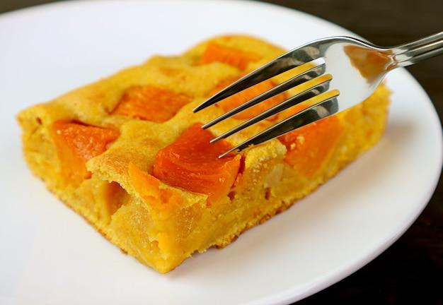 Fetta di gustosa e sana torta di zucca fatta in casa bar su un piatto bianco