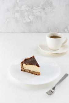 Fetta di tofu cheesecake con caramello salato su un piatto bianco con una tazza di tè