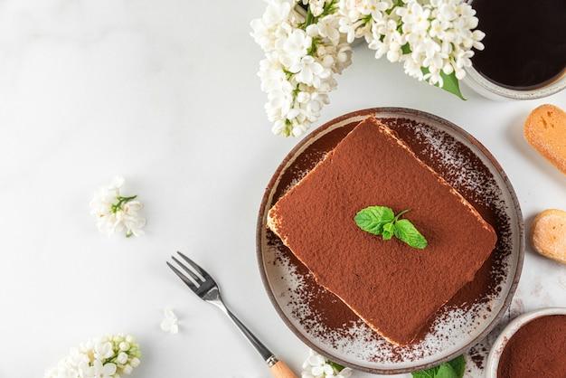 Fetta di tiramisù tradizionale italiano da dessert in un piatto con tazza di caffè, forchetta da dessert e fiori su superficie bianca per una gustosa colazione
