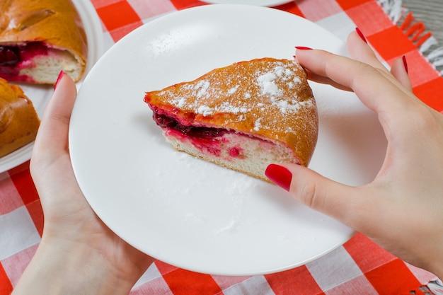 Fetta di delizioso pezzo di torta di ciliegie con zucchero poedered nelle mani di una donna su una tovaglia a scacchi