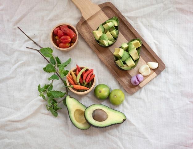 Avocado a fette, scalogno e aglio messi su un vassoio di legno accanto a pomodoro, peperoncino e limone. ingrediente per cucinare insalata piccante
