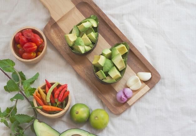Avocado a fette, scalogno e aglio messi su un vassoio di legno accanto a pomodoro, peperoncino e lime ingredienti per cucinare insalata piccante