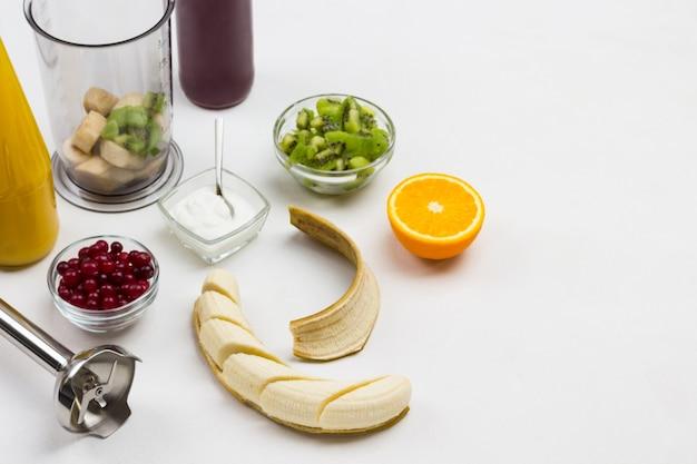 Banana a fette e buccia. mezza arancia. mirtilli rossi e kiwi in ciotole. frullatore e caraffa per frullatore a banana. ingredienti per preparare frullati di frutta. vista dall'alto. copia spazio