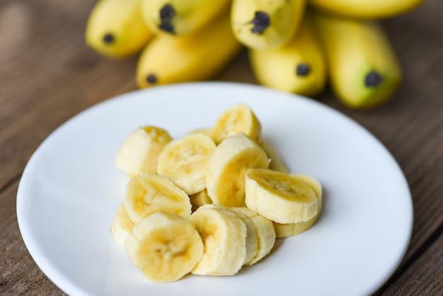 Buccia di banana affettata sul piatto bianco e fondo di legno, banana sbucciata pronta da mangiare
