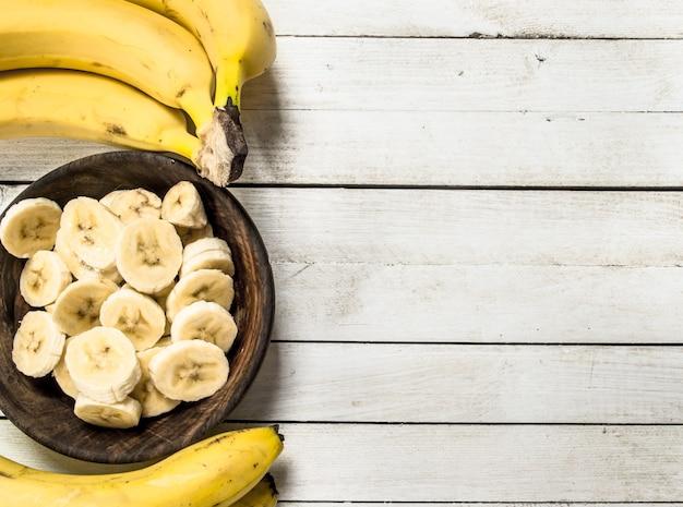 Banane a fette in una ciotola di legno. su uno sfondo di legno bianco.