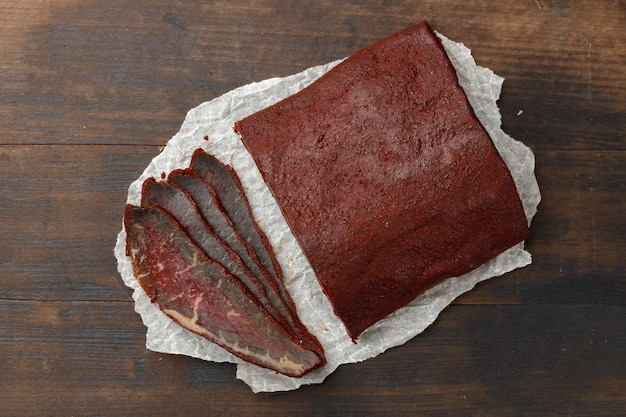 Carne di basturma affettata su fondo di legno della fronte