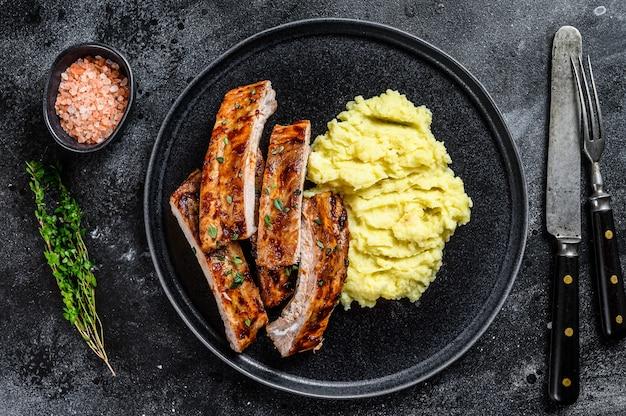 Fette di carne di maiale alla griglia barbecue costine di maiale su un piatto con purè di patate. sfondo nero. vista dall'alto.
