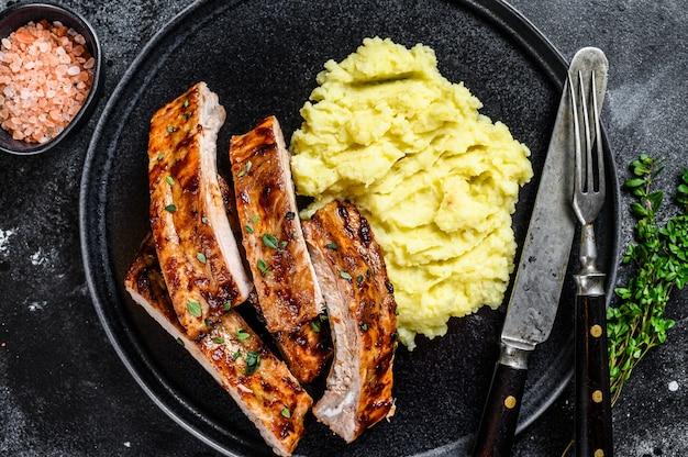 Fette di carne di maiale alla griglia barbecue costine di maiale su un piatto con purè di patate.