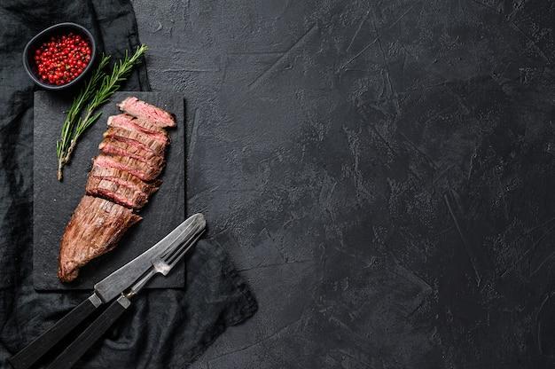Bistecca di manzo affettata mediamente cotta. sfondo nero. vista dall'alto. spazio per il testo
