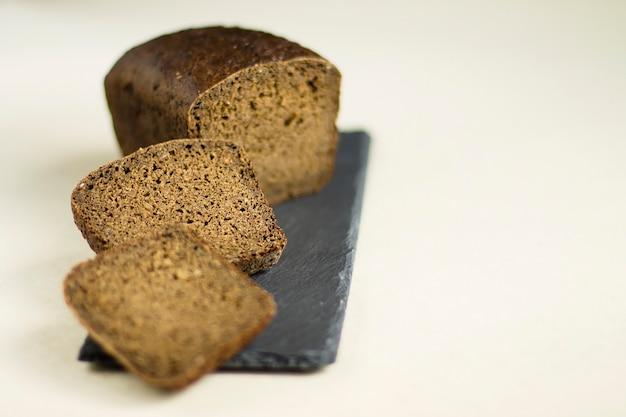 Pane nero a fette, su una tavola grigia.