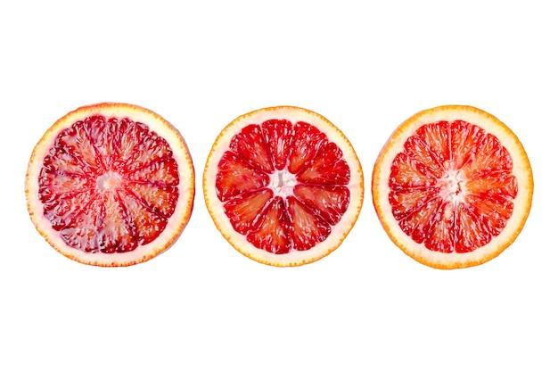 Arance sanguinanti affettate isolate su fondo bianco, arancia siciliana rossa matura fresca, agrumi.