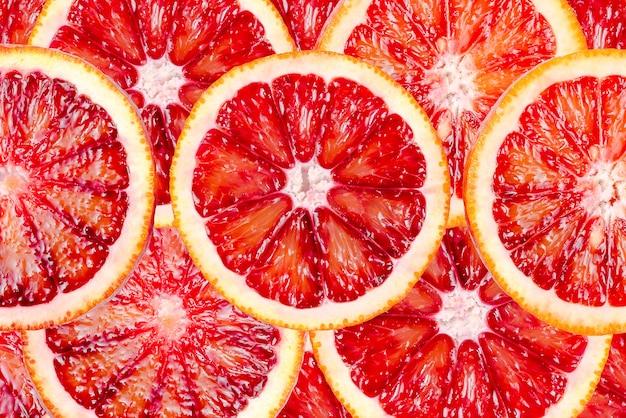 Fette di arance sanguinanti texture, arancia siciliana rossa matura fresca, agrumi per lo sfondo.