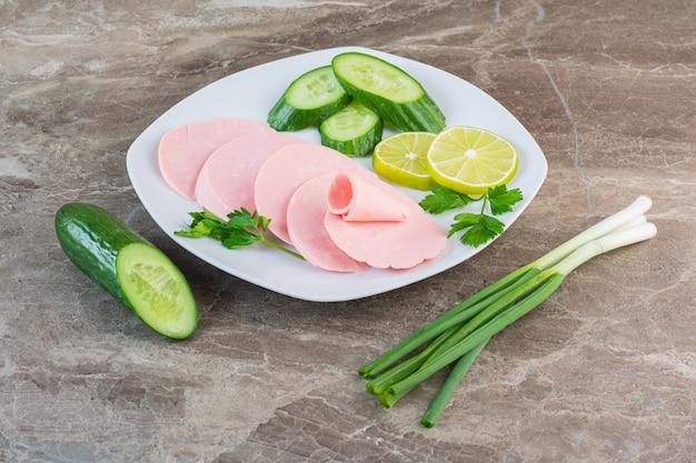 Salsiccia bollita affettata, prezzemolo, cetriolo e cipolle verdi su un piatto sulla superficie di marmo