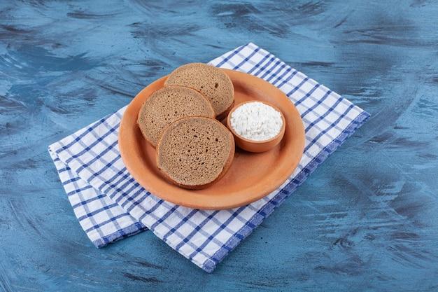 Fette di pane e una ciotola di farina su un piatto su uno strofinaccio, sul blu.