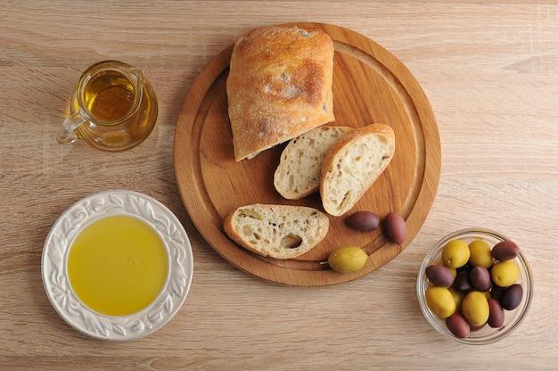 Ciabatta di pane a fette su tavola rotonda, olive e olio extra vergine di oliva