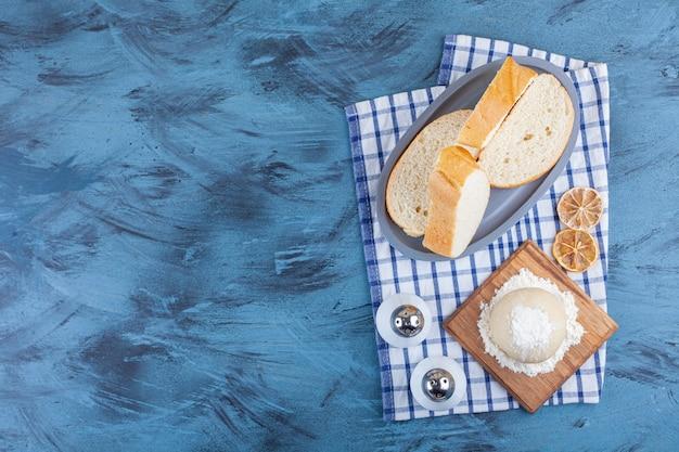 Fette di pane accanto all'impasto su una tavola su un asciugamano, su sfondo blu.