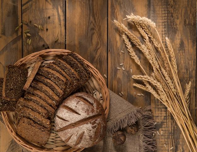 Pane a fette in un vassoio di vimini con superficie in legno di spighette con un panno