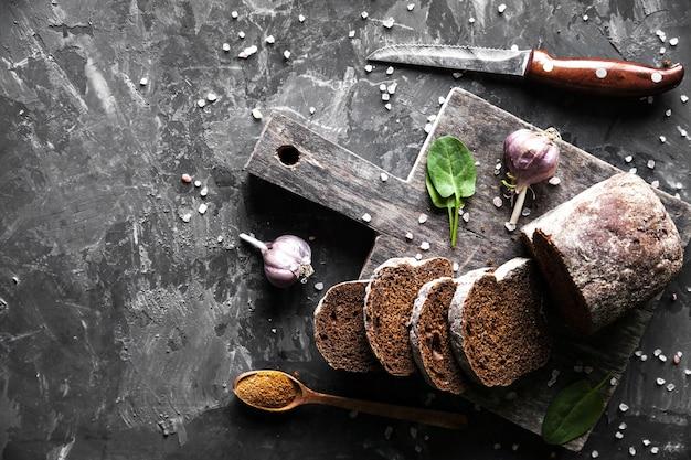 Fette di pane con burro e pezzi sparsi su uno sfondo scuro