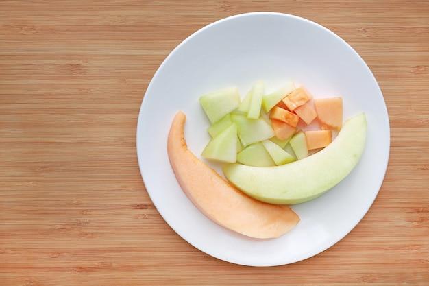 Melone affettato del cantalupo sul piatto bianco contro fondo di legno.