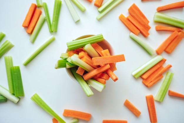 Carote affettate e sedano in una ciotola bianca, cibo sano, sfondo colorato ricetta