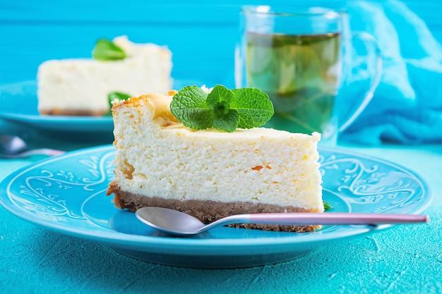 Cheesecake a fette. deliziosa cheesecake dolce con tè alla menta su blu