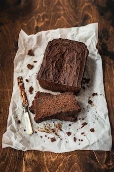 Torta al cioccolato a fette e un coltello su carta da forno sul tavolo di legno scuro