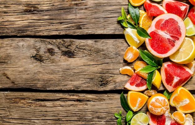 Agrumi a fette - pompelmo, arancia, mandarino, limone, lime con foglie