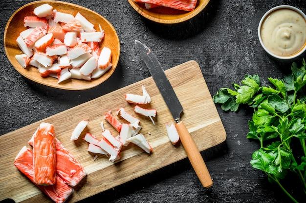 Bastoncini di granchio a fette su un tagliere con un coltello. sulla tavola rustica nera