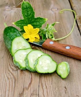 Cetriolo affettato con fiore giallo e foglia verde, coltello su una tavola di legno