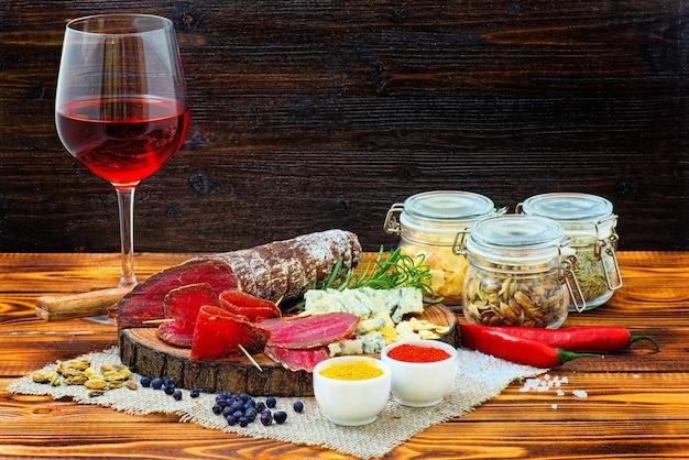 Bresaola stagionata affettata con spezie e un bicchiere di vino rosso su fondo rustico in legno scuro.