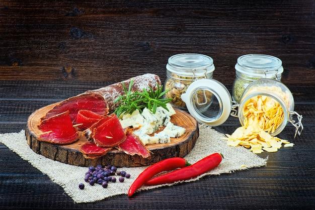 Bresaola stagionata affettata con spezie e un rametto di rosmarino su fondo rustico in legno scuro.